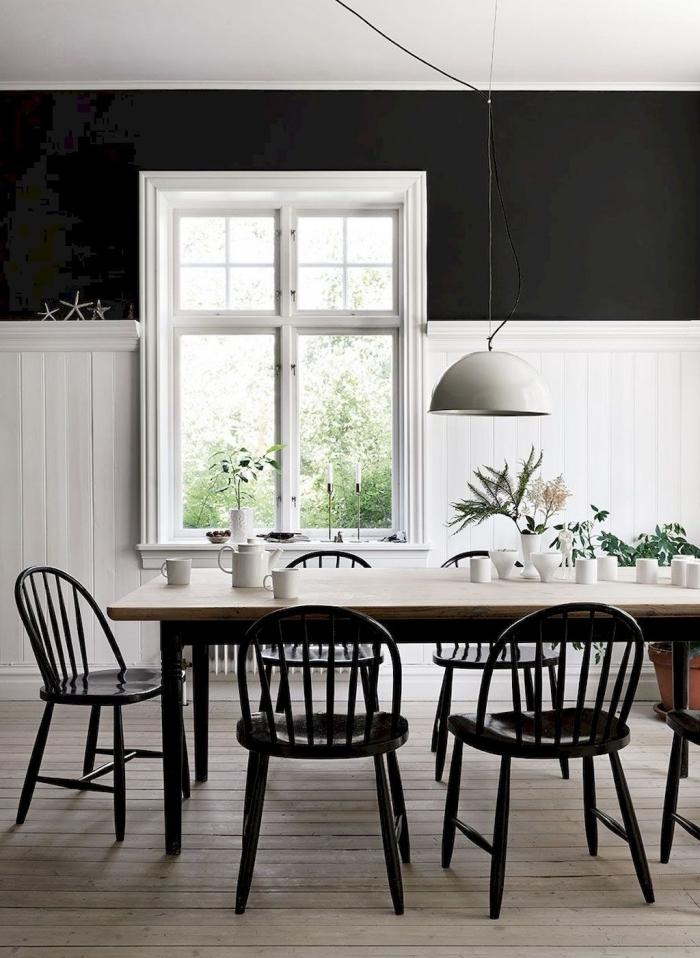 une salle à manger vintage scandinave avec un mur bicolore associant un lambris blanc et une peinture noire dans sa partie haute