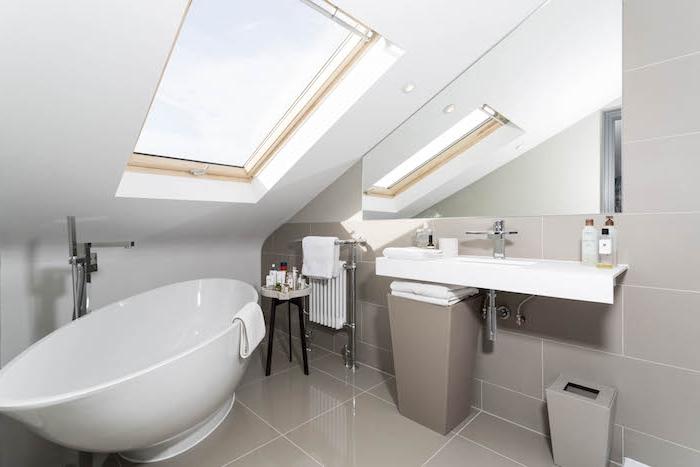 baignoire sous pente couleur blanche dans une salle de bain gris et blanc, carrelage sol gris, miroir sous pente, murs blancs
