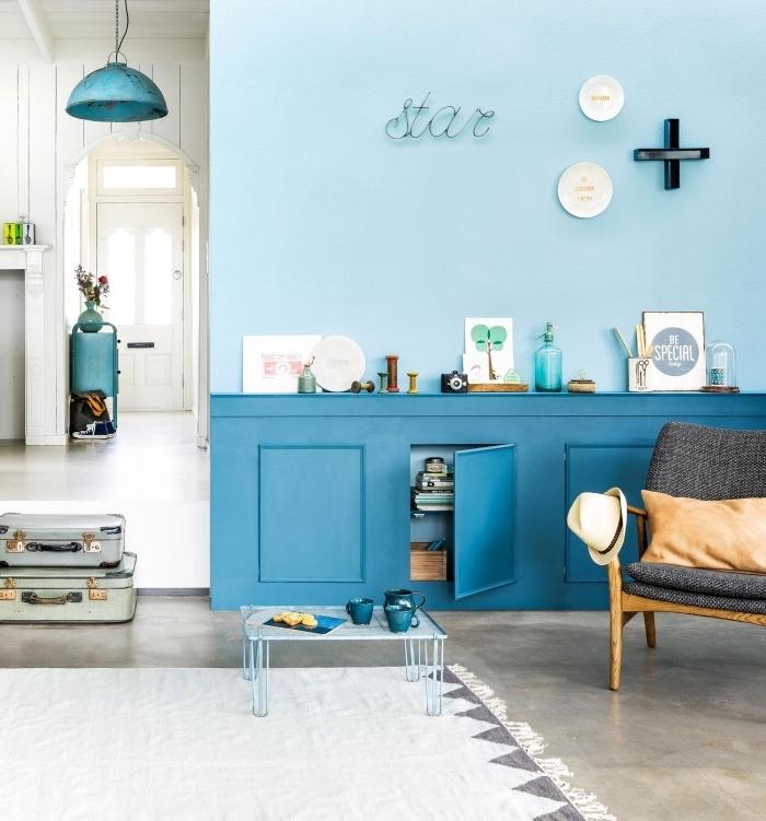 mur bicolore en nuances du bleu sarcelle qui illumine le salon de style vintage, soubassement en avec espace rangement intégré