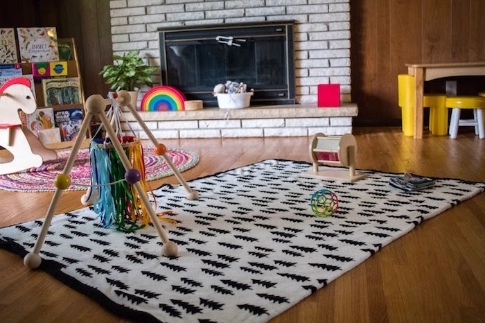 tapis d'éveil montessori avec un mobile montessori intéressant, tapis rond, cheval à bascule, cheminée salon