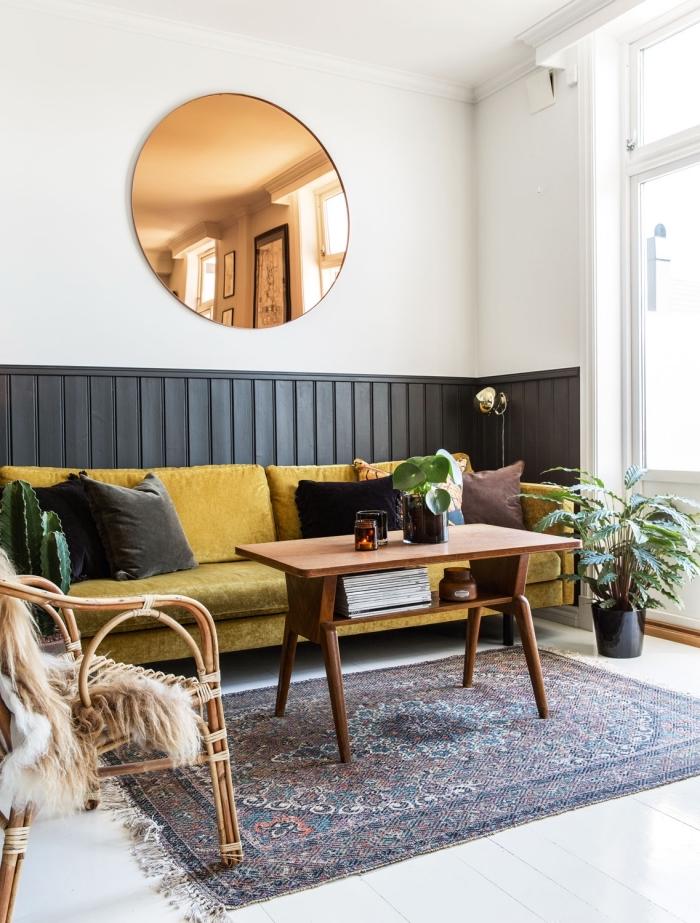 du lambris noir en soubassement qui délimite l'espace dédié au canapé dans un salon vintage scandinave, peinture lambris tendance