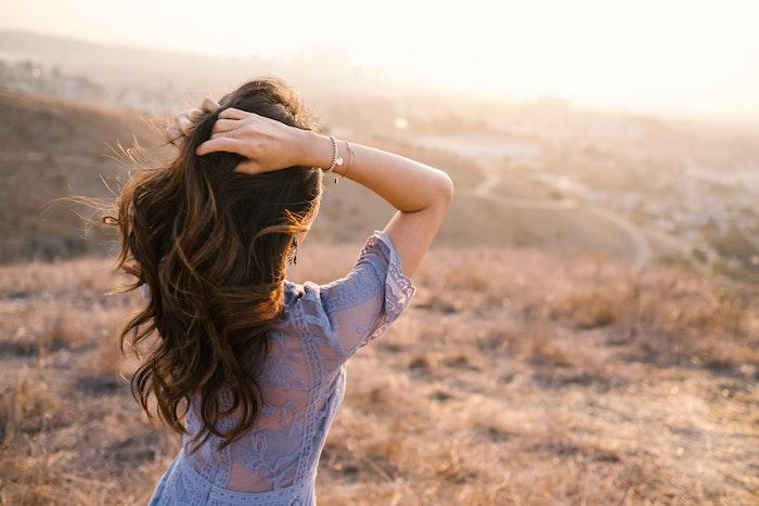 Belle photographie de femme cheveux longs qui regarde le coucher du soleil, chouette robe noire dentelle, robe boheme longue décontracté chic