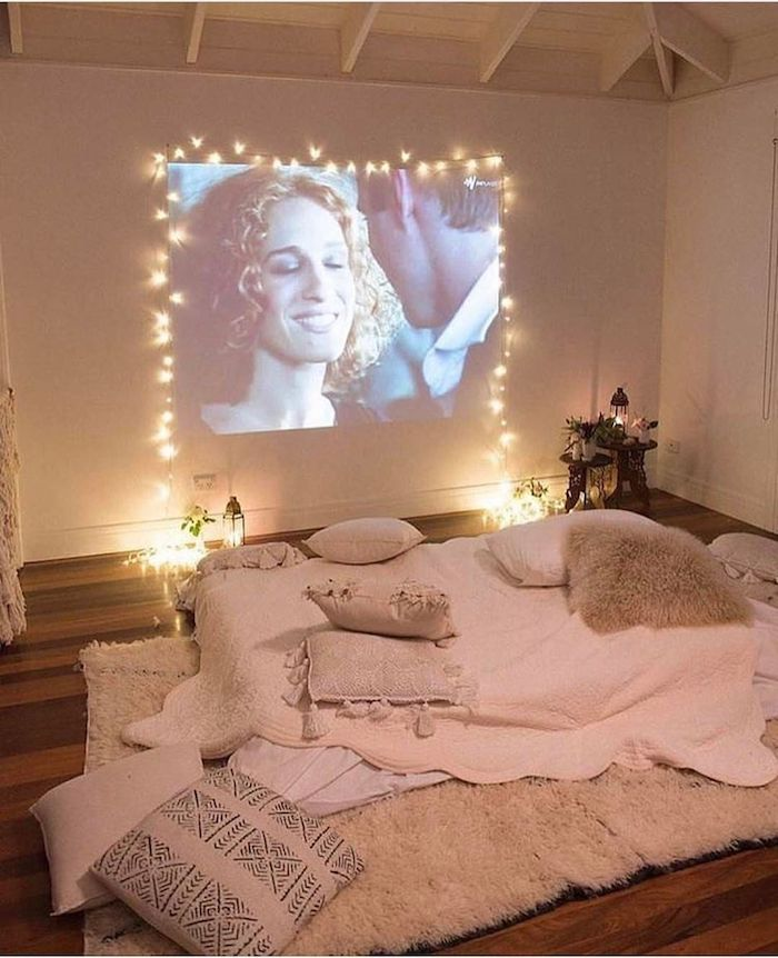 Projecteur vintage, mur avec projection de film cadré avec une guirlande lumineuse, coin cosy sur le sol avec beaucoup de coussins