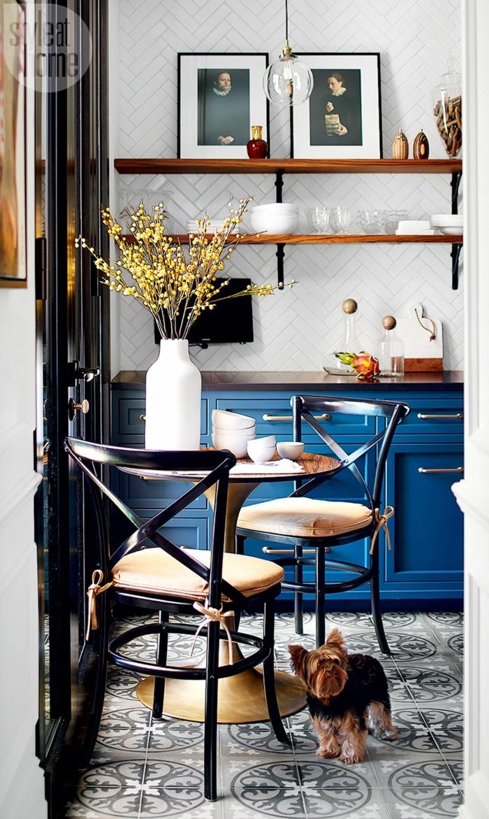 cuisine en bleu et blanc, étagères en bois, vase blanc avec fleurs, petite table ronde, meuble bistrot bleu