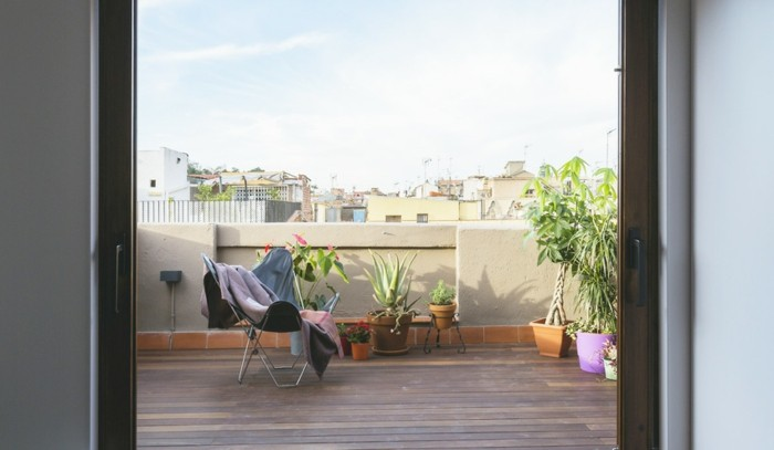 chaise pliante style scandinave sur une terrasse en bois avec des plantes vertes en pots de fleurs, garde corps beton