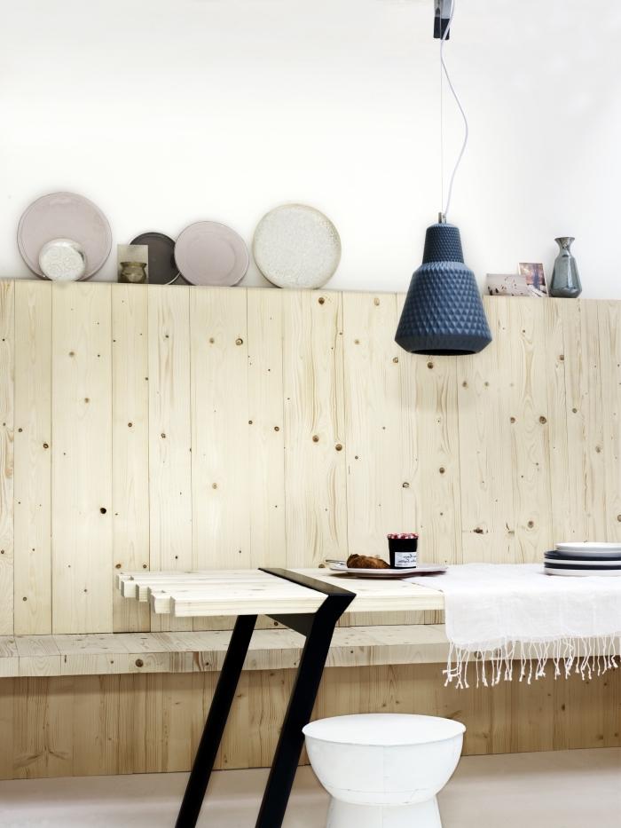 mur avec un soubassement bois naturel qui fait office d'étagère murale avec banc intégré