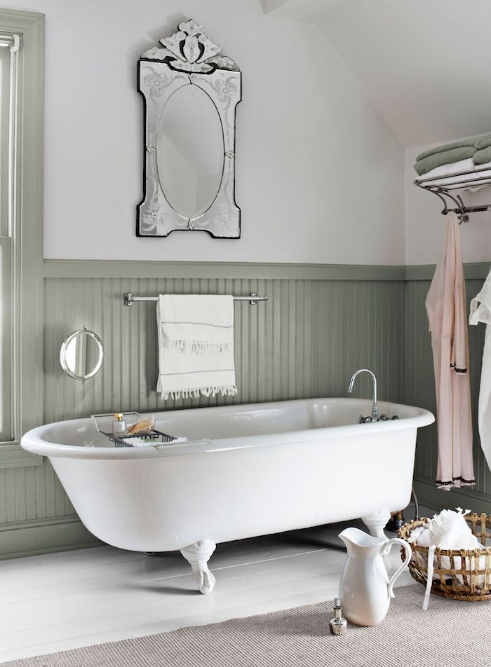 baignoire blanche dans une salle de bain sous pente blanche et grise avec soubassement bois repeint en gris, miroir vintage, tapis gris sur parquet blanchi