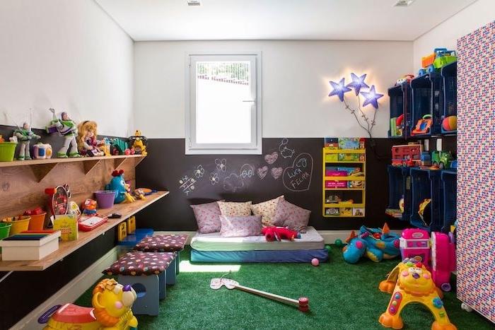 pan de mur soubassement en peinture ardoise avec dessins enfant, rangements étagère et cagettes en plastique, tapis imitation herbe, jouets enfant