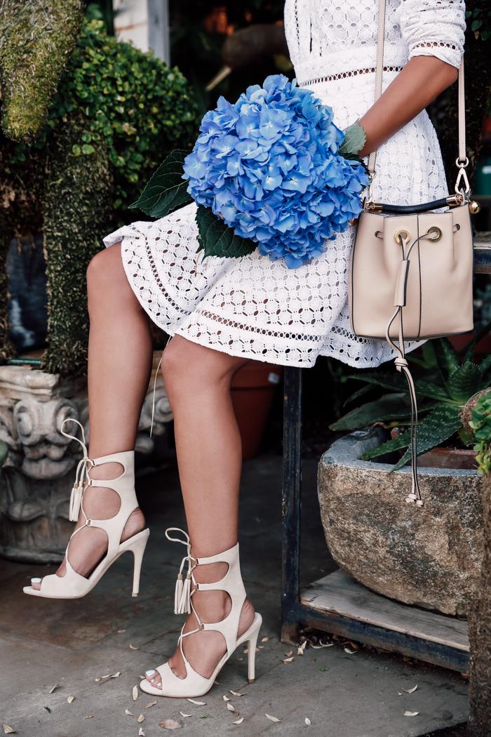 Bouquet hortensia dans les mains d'une femme bien habillée en robe blanche courte joliment accessoirisé, chaussures à talon et sac à main classe beiges