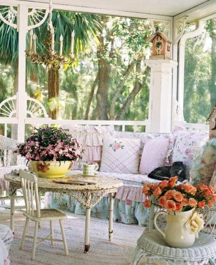 aménagement petite terrasse dans un style shabby chic avec des coussins fleuris rangés sur un canapé, table et chaise basse