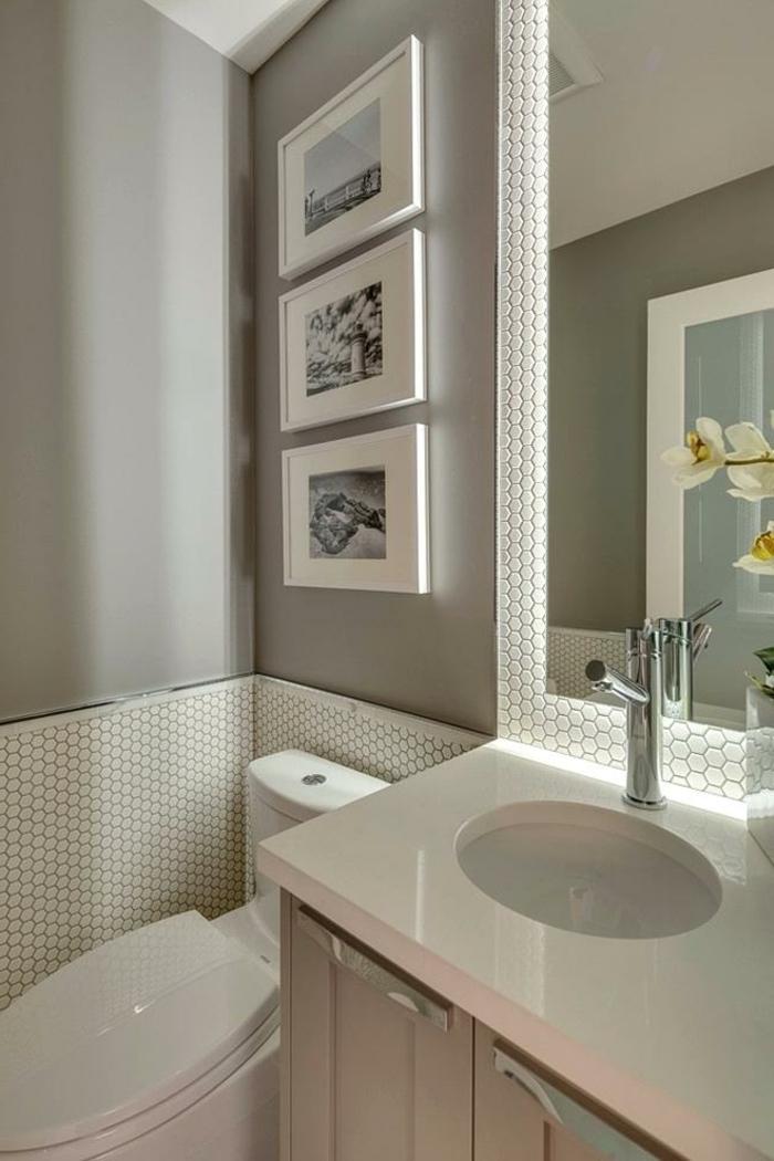 grand miroir mural, petites tomettes blanches, trois tableaux monochromes, robinet chromé
