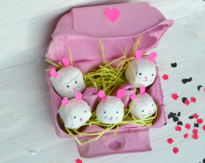 petits lapins en papier mâché cachés dans un carton à oeufs peint rose, oreilles roses et herbe artificielle