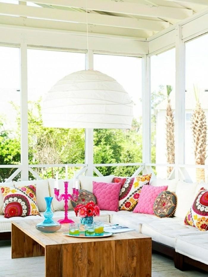 canapé d angle en marron et blanc décoré de coussins orientaux, table basse bois sur un revetement bois blanchi