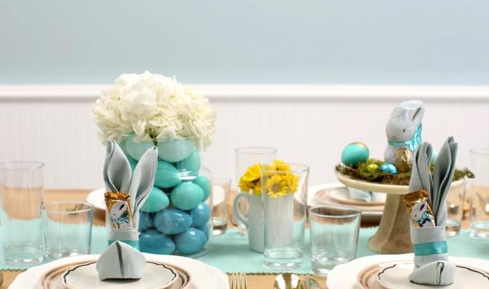 une belle décoration de table de pâques aux nuances du vert d'eau, modèle de pliage serviette lapin avec pochette