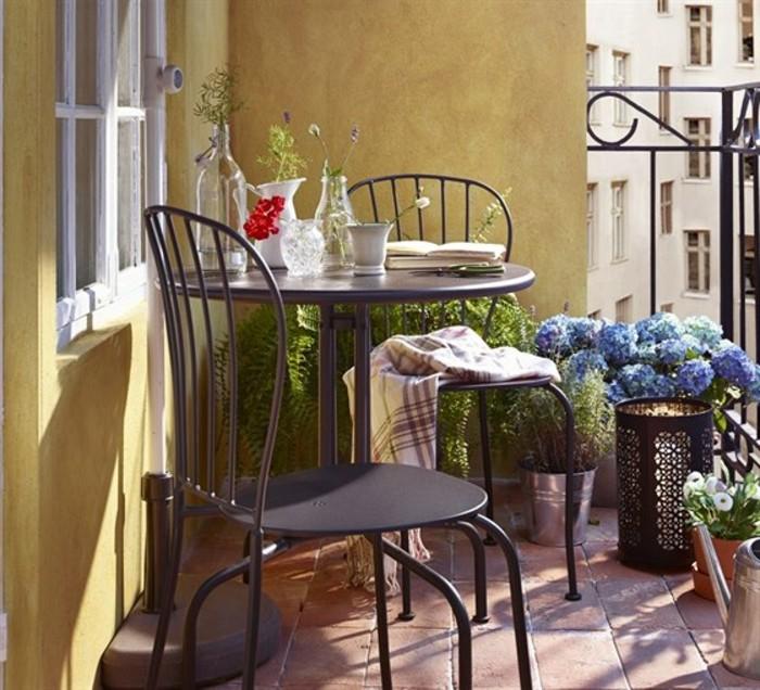 table et chaises metalliques gris foncé sur un carrelage grès cérame, murs jaunes, plantes en pots, garde corps metalliques