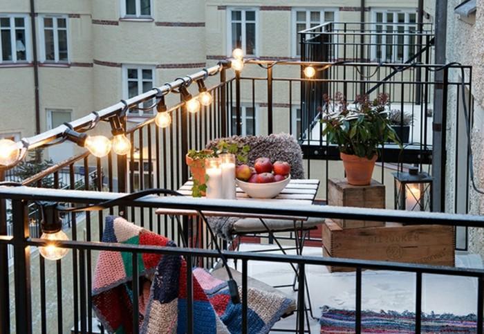 garde corps décoré d ampoules electriques, chaises et table en bois et metal, deco de bougies, plantes cagettes de bois
