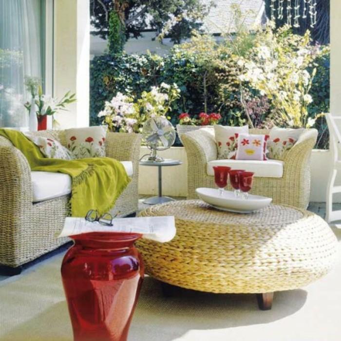 fauteuil, canapé et chaises en rotin avec des coussins d assise blancs et coussins décoratifs à motifs fleuris, tapis blanc et grand vase rouge