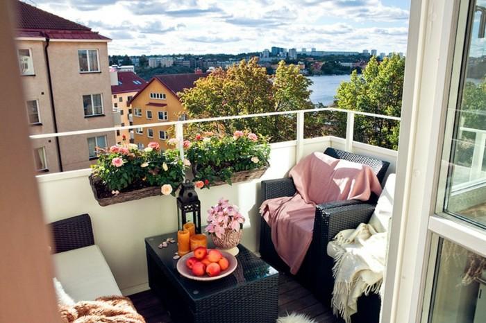 decoration balcon avec fauteuils et table basse noirs avec deco de plaids moelleux, deco de bacs à fleurs suspendus, sol bois marron usé