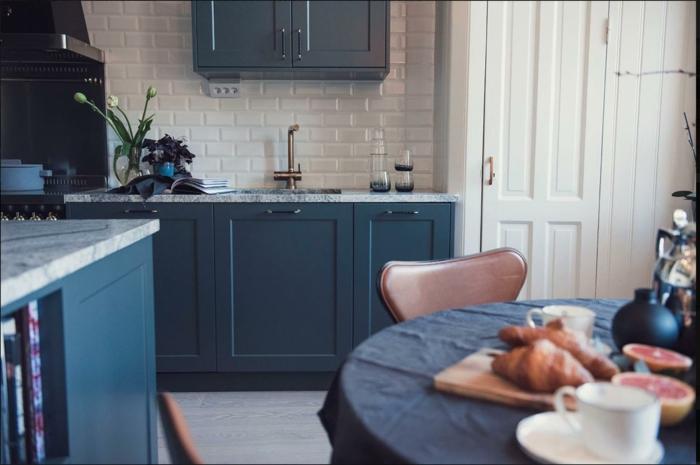 amenagement petite cuisine en bleu et blanc, table ronde, nappe bleue, chaises en cuir, carrelage métro, robinet vintage