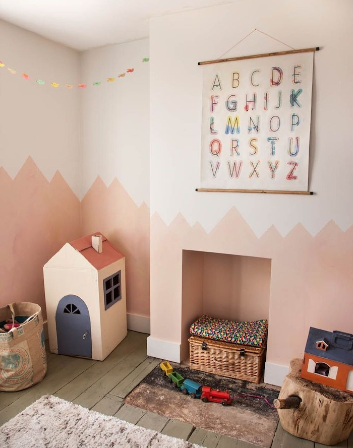chambre vintage avec ambiance montessori, mur repeint en rose clair et foncé, parquet usé, bac à jouets original, maisonnette carton, tronc d arbre en guise de tabouret, panier rangement par sol