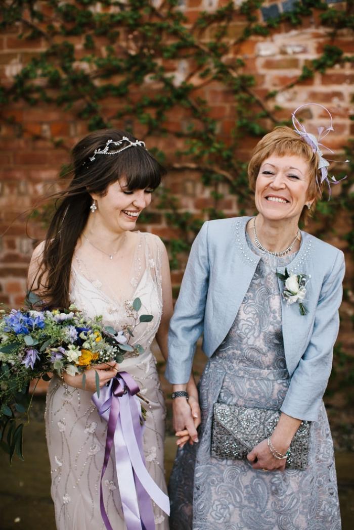 tenue mariage femme 50 ans composée d'une robe courte bleu et gris argent à broderies et sa veste courte coupée au niveau de la taille