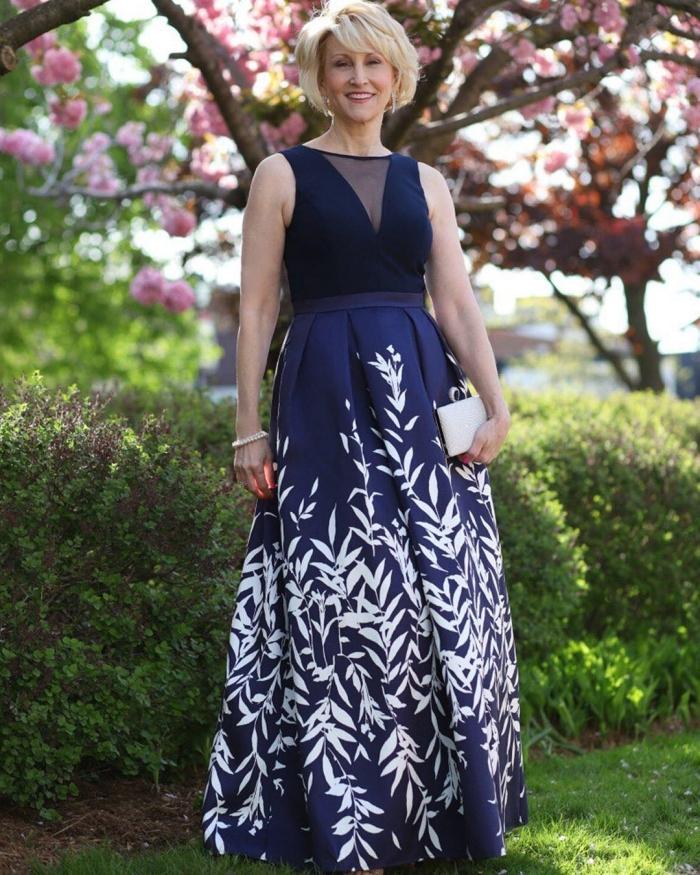 une robe de cérémonie longue de couleur bleu marine avec jupe évasée couverte d'imprimés végétaux blancs et un joli top à décolleté en v effet transparent, modèle de robe ceremonie femme 50 ans qui met en valeur la taille