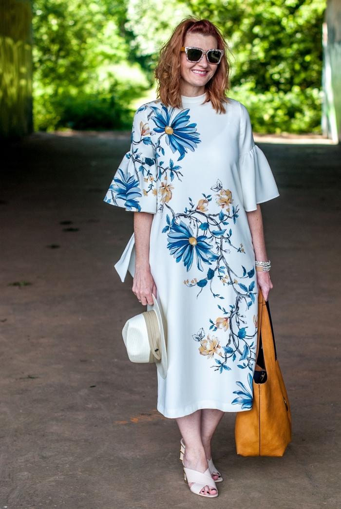 une robe invitée mariage blanche aux imprimés floraux, de coupe droite fluide et de longueur midi avec des manches fantaisie évasées