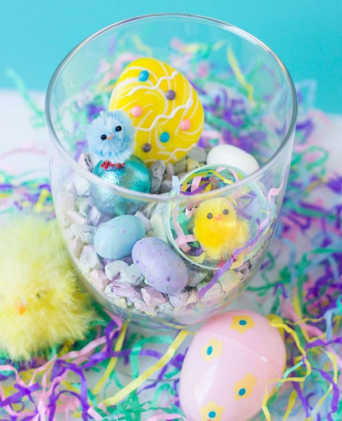 petit terrarium en verre rempli de gravier coloré, oeufs colorés et petites figurines de poussins, activité paques maternelle facile