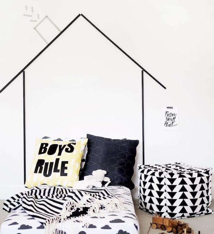 tete de lit enfant scandinave en bandes de washi tape sur mur blanc pour figurer une maisonnette, matelas noir et blanc, coussins decoratifs et pouf noir et blanc