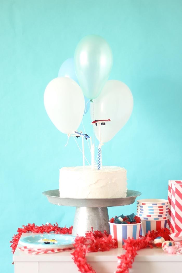 gâteau anniversaire garçon au glaçage blanc sur le thème avion décoré de petits ballons et de figurines avions