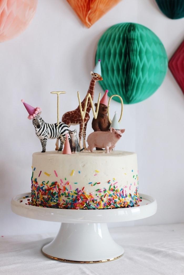 theme anniversaire les animaux, gâteau d'anniversaire au glaçage de crème beurre et vermicelles en sucre décoré de figurines d'animaux