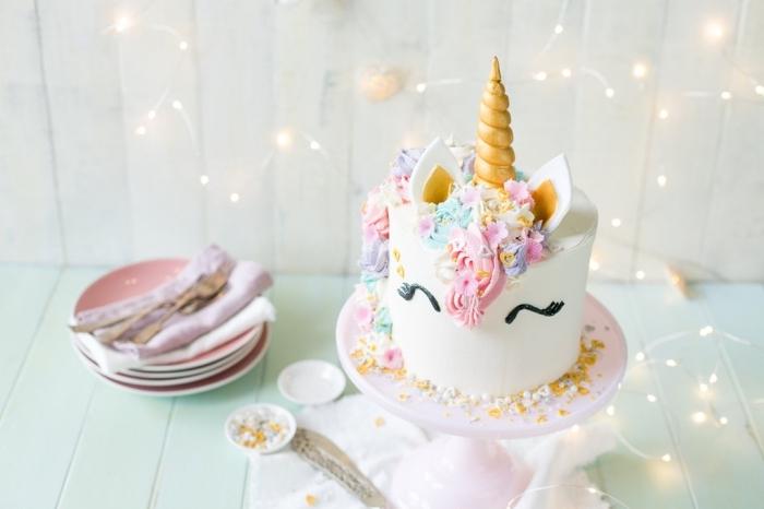 gâteau d'anniversaire en forme de tête de licorne au glaçage lisse blanc avec une crinière arc-en-ciel réalisée à la poche à douille, theme anniversaire licorne
