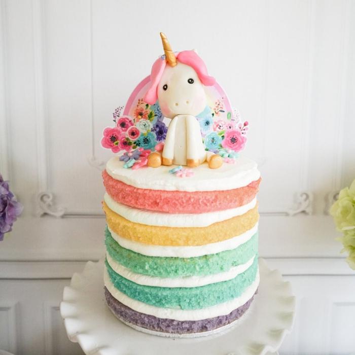 gâteau arc-en-ciel orné d'un cake topper original et d'une figurine licorne en pâte à sucre pour un theme anniversaire licorne