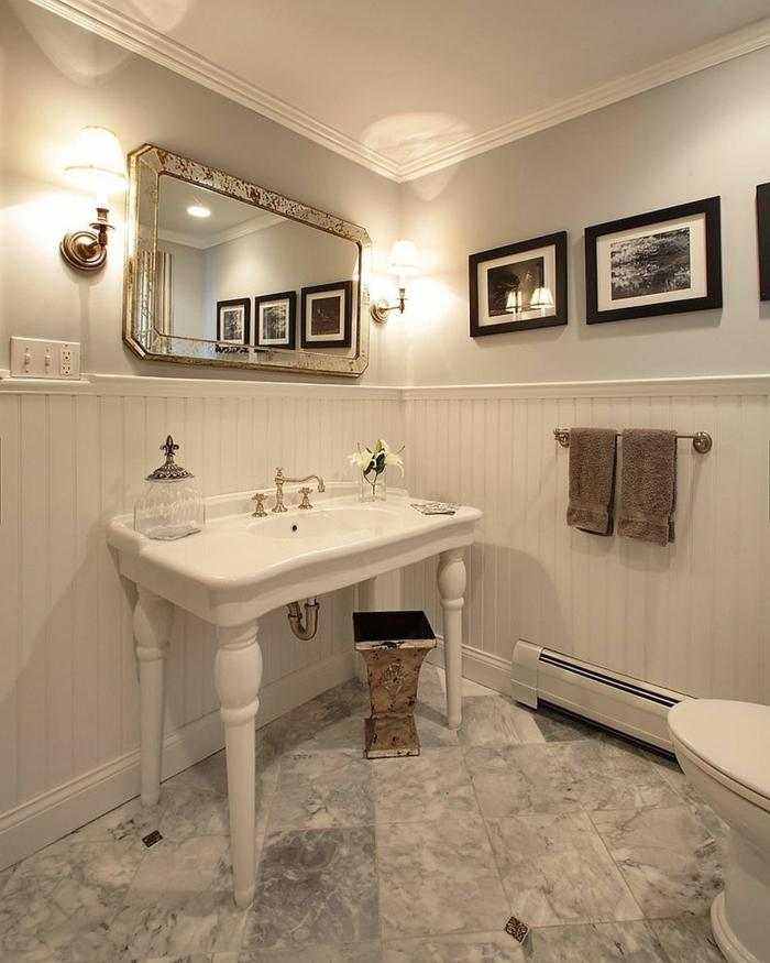 vasque quetre pieds blanche, miroir encadré cadre argent, peintures monochromes, soubassement blanc