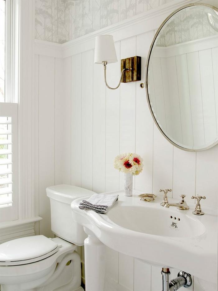 jolie décoration wc en blanc, miroir rond, vasque vintage à quatre pieds, lambris mural blanc, robinetterie rétro