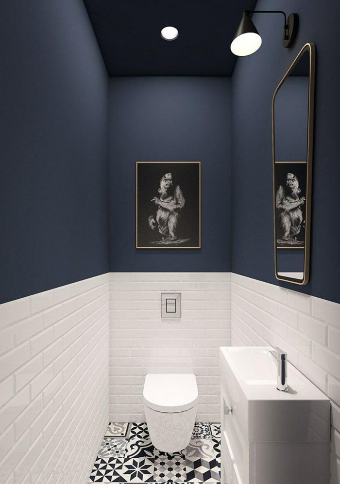 amenagement toilette en bleu et blanc, carreaux métro blancs, miroir encadré, sol carreaux de ciment