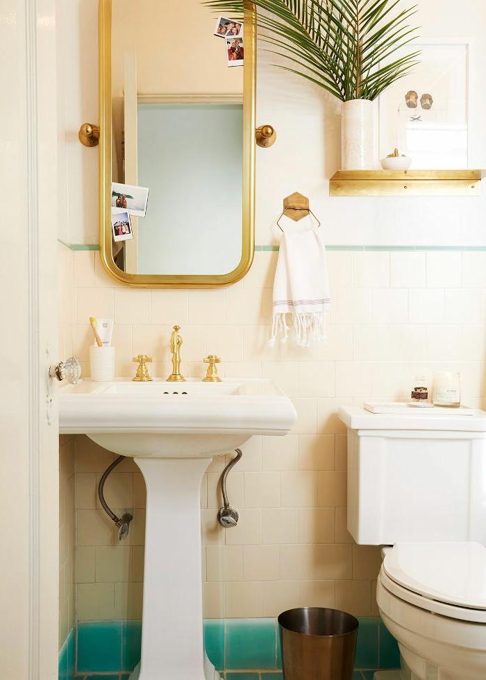 miroir encadré, robinets finition or, vasque blanche, petite étagère, vase avec une feuille exotique, decoration wc