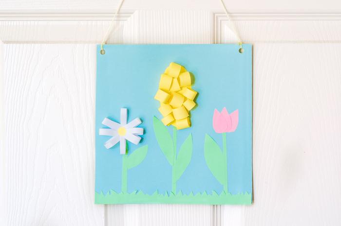 tableau decoratif de printemps en tulipe, jacinthe et marguerite, fleurs de papier sur fond bleu, activité manuelle primaire