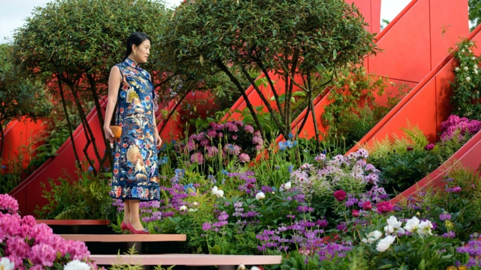 escalier flottant dans un jardin aux fleurs magnifiques, arbres, jeune femme qui se promène