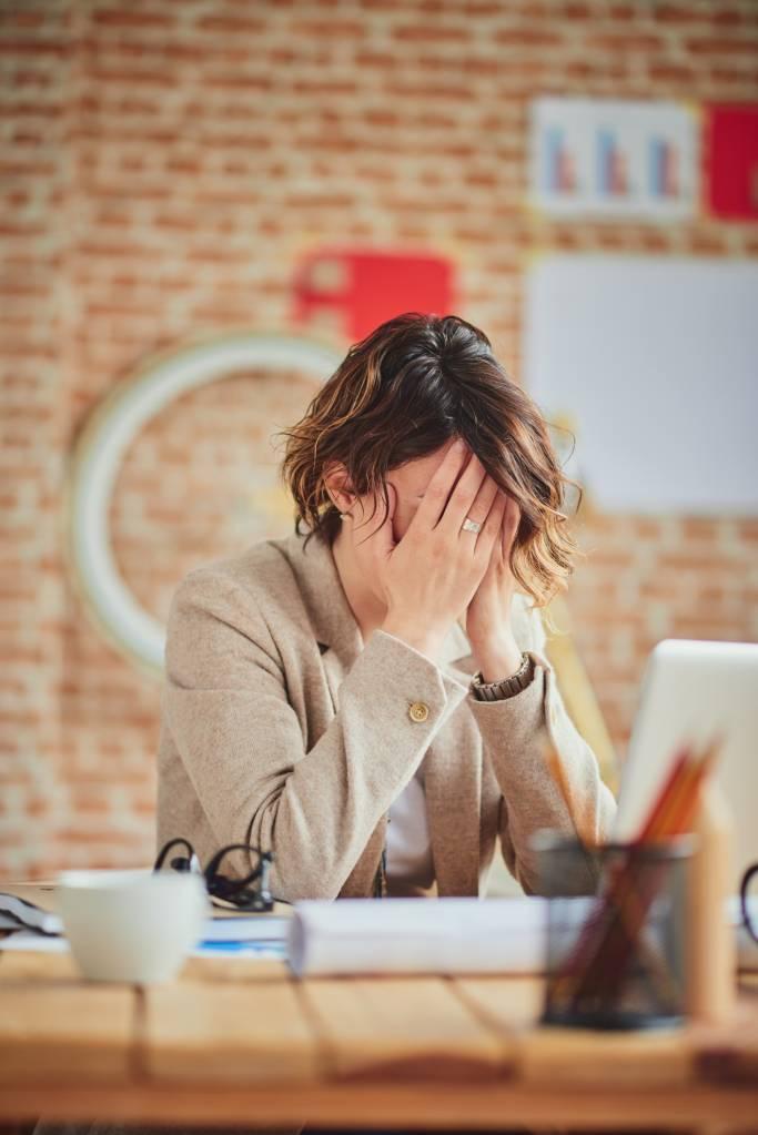 femme avec cheveux cours assiet sur le bureau de travail, bureau de travail en bois clair, mur en briques, femme stressée