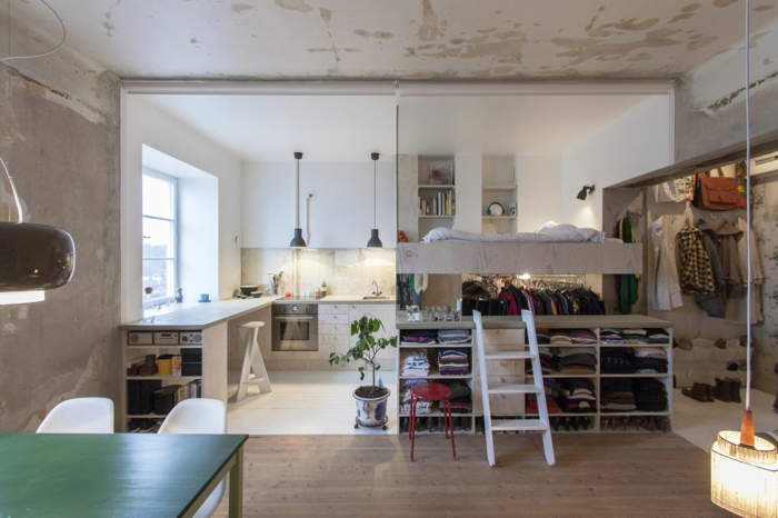 kitchenette en angle blanche, lit flottant et étagère originale, plafond en béton, dressing ouvert