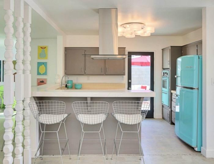 petit studio moderne aux accents colorés, chaises de bar basket, îlot de cuisine blanc, placards couleur taupe