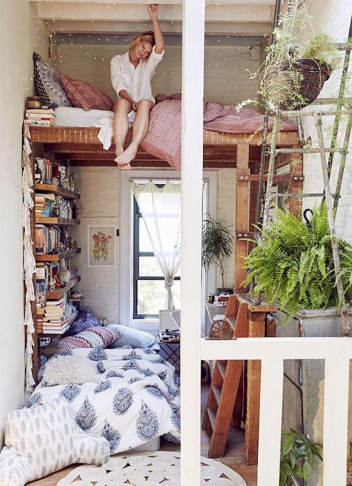 deco cocooning de petit studio avec lit bois en hauteur au dessus d un coin cosy avec canapé par sol et bibliothèque de livres