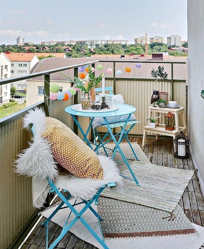 guirlande boules colorées sur un balcon aménagé avec table et chaises metal bleues et tapis gris sur sol en bois, petite etagere rangement plantes et deco