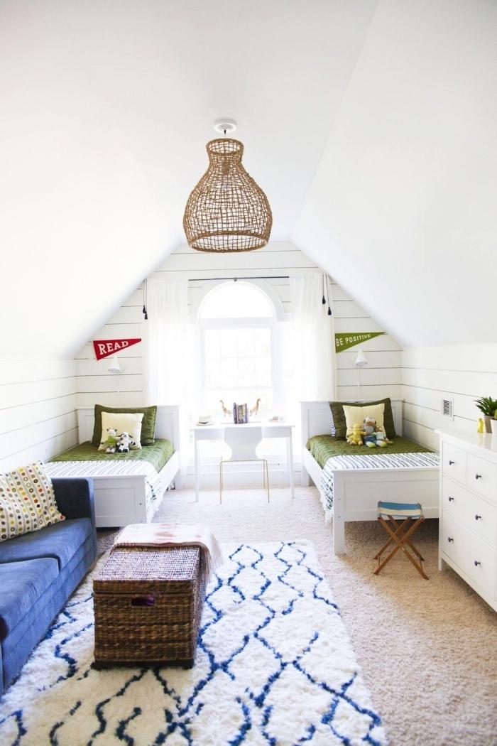 une chambre d'enfant mansardée pour deux de style bord de mer avec deux lits posés au fond de la pièce près de la fenêtre