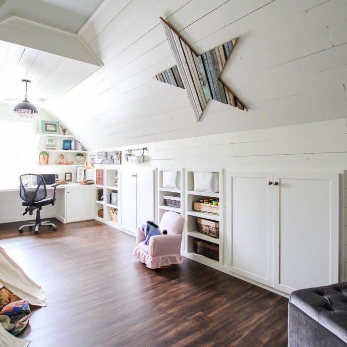 une chambre d'enfant mansardée avec parquet en bois foncé, aux murs recouverts de planches de bois blanc, une chambre mansardée avec espace bureau et meuble sous pente bas intégré au mur