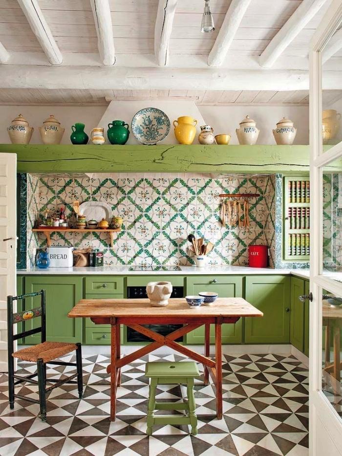 une cuisine de style campagne équipée d'une credence carreaux ciments à motifs vintage en vert et blanc qui s'harmonisent avec les placards couleur vert anis