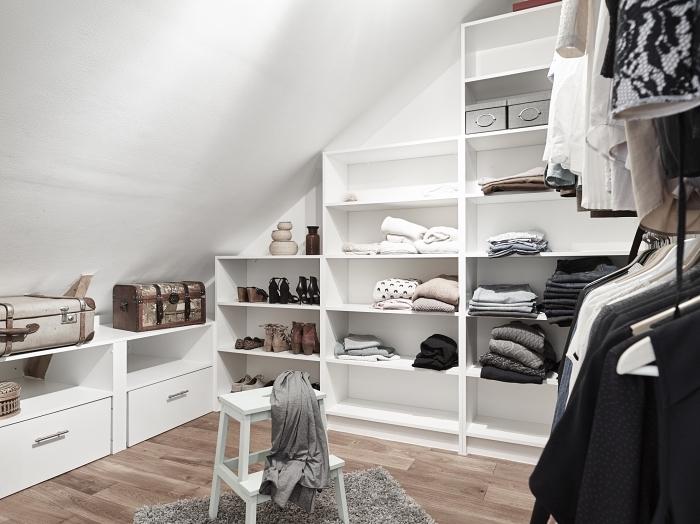 une pièce dressing sous pente avec étagères modulables et des tringles à vêtements