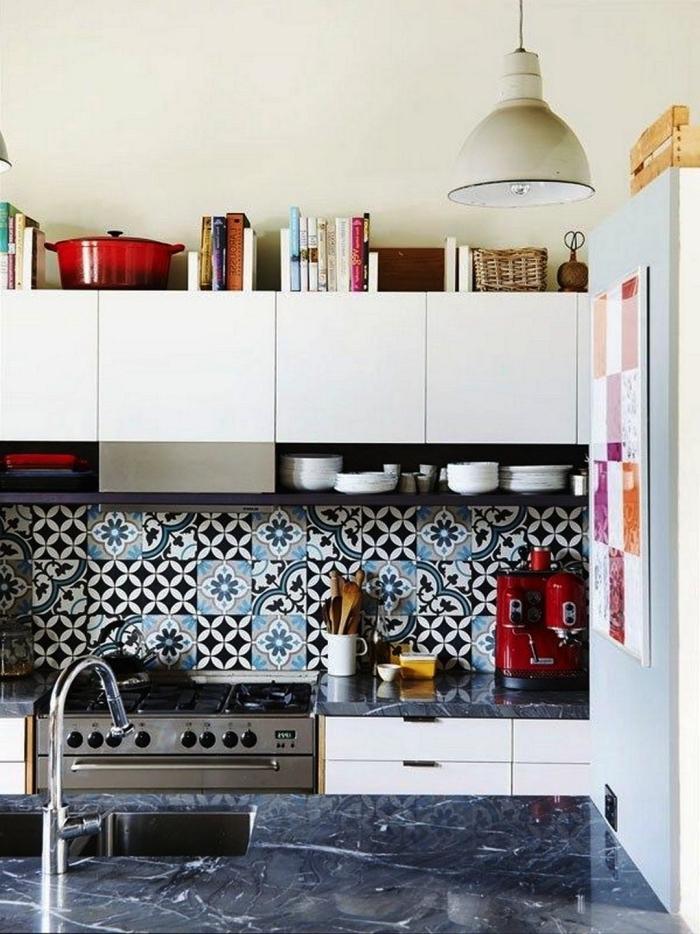 une credence de cuisine en carreaux de ciment adhesif aux motifs variés en noir et bleu qui dynamise l'ambiance monochrome