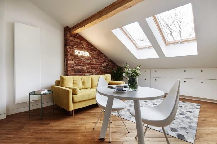 aménagement gain de place et fonctionnel d'un salon mansardé de style scandinave, placard sous pente qui se fond dans le décor